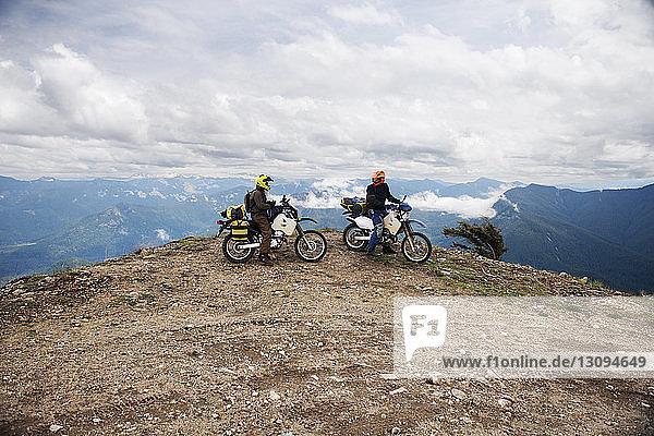 Freunde fahren Motorrad auf Klippe gegen bewölkten Himmel