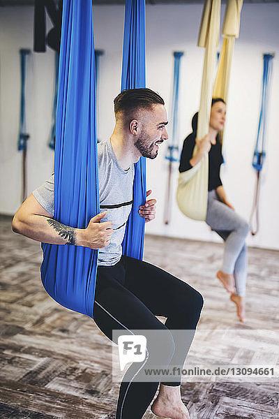 Freunde sitzen auf Hängematten  während sie im Fitnessstudio trainieren