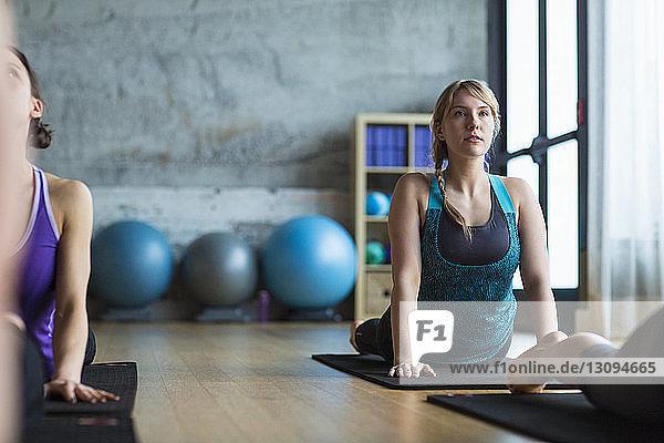 Women practicing upward facing dog position in gym