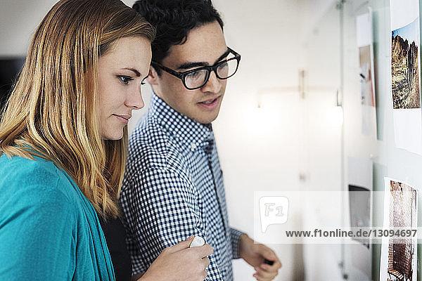 Lächelnde Geschäftsleute planen über Fotos am Whiteboard im Büro