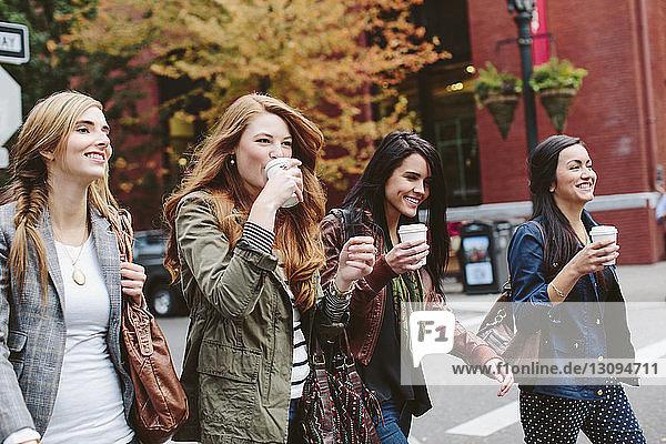 Glückliche Freundinnen trinken Kaffee beim Spaziergang auf der Straße
