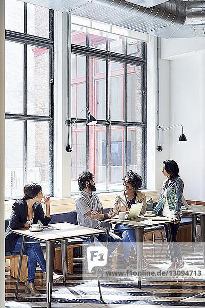 Geschäftsleute diskutieren während einer Besprechung in der Büro-Cafeteria