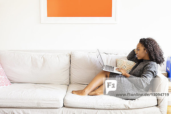 Side view of woman using laptop computer while sitting on sofa