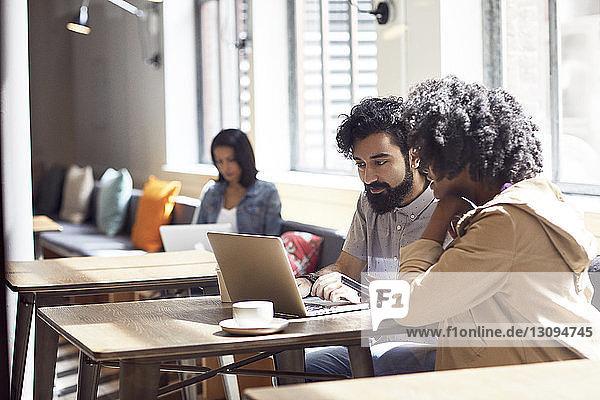 Geschäftsleute  die an einem Laptop-Computer arbeiten  während eine Kollegin im Hintergrund sitzt