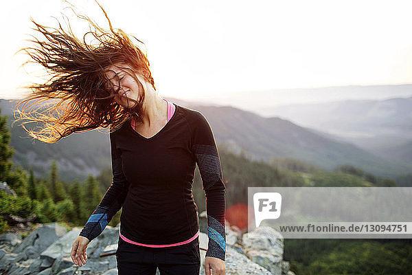 Glückliche Frau schüttelt den Kopf  während sie auf einer Klippe vor klarem Himmel steht