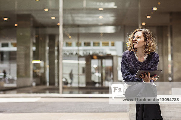 Frau benutzt Tablet-Computer  während sie auf einem Sitz sitzt
