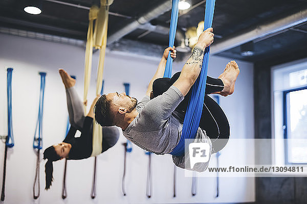 Freunde hängen in Hängematten  während sie im Fitnessstudio Luftyoga praktizieren