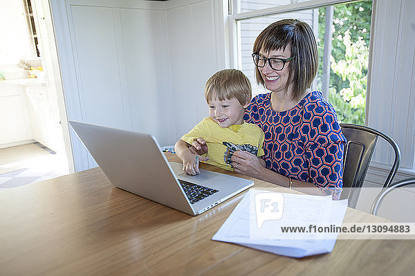 Smiling mother with son using laptop computer on table at home