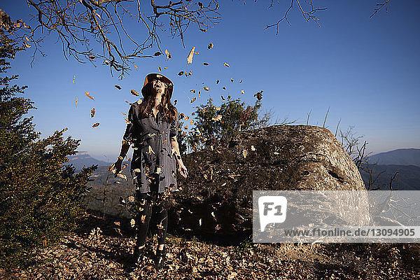 Glückliche Frau spielt mit Blättern  während sie auf einer Klippe vor klarem blauen Himmel steht