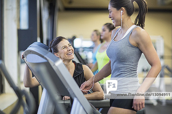 Instructor talking to woman exercising on treadmill in gym