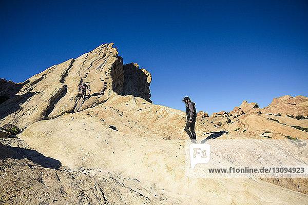 Freunde wandern auf Felsformationen bei strahlend blauem Himmel am sonnigen Tag