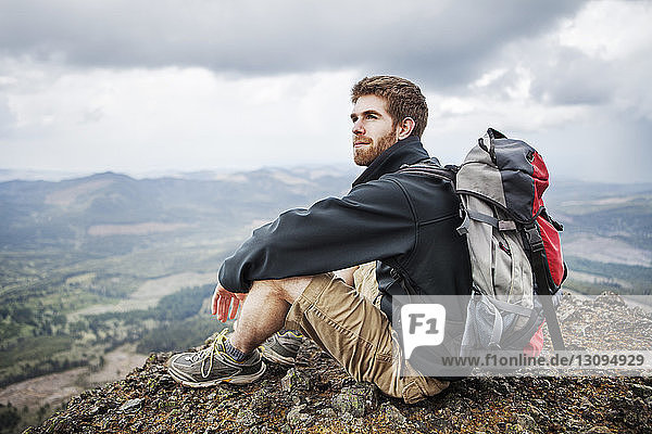 Thoughtful man with backpack sitting on mountain