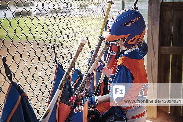 Seitenansicht eines Jungen  der auf dem Spielfeld den Baseballschläger aus der Tasche nimmt