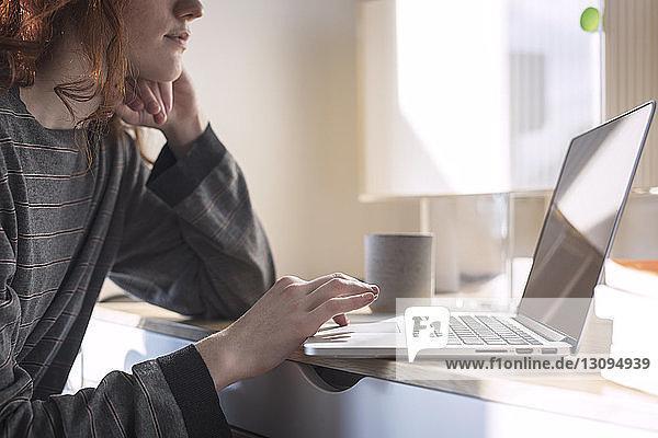 Mittelgruppe von Frauen  die zu Hause einen Laptop-Computer benutzen
