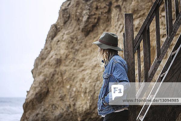 Seitenansicht eines Mannes  der an Holzstufen am Strand steht