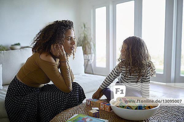 Mutter und Tochter unterhalten sich beim Spielen mit Spielzeugklötzen zu Hause