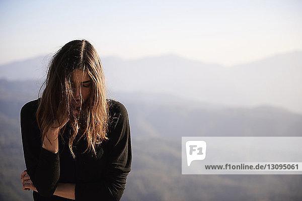 Frau mit geschlossenen Augen an Bergen stehend