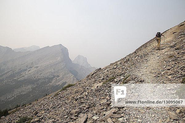 Rückansicht eines Wanderers  der am Berg gegen den Himmel klettert