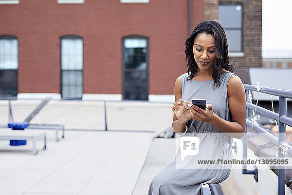 Businesswoman using smart phone while sitting railing at building terrace