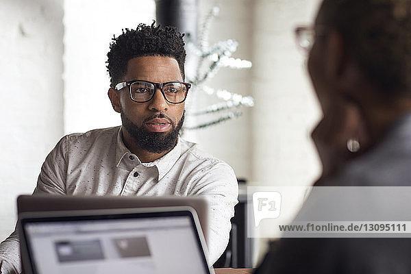 Junger Mann spricht mit Frau  während er zu Hause einen Laptop benutzt