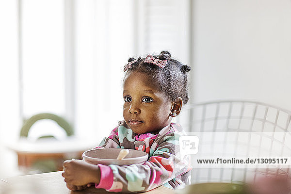 Thoughtful girl holding breakfast bowl at table in kitchen