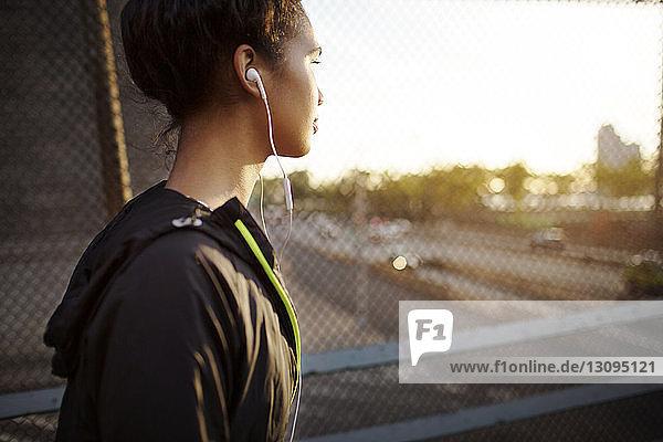 Seitenansicht einer Joggerin beim Musikhören