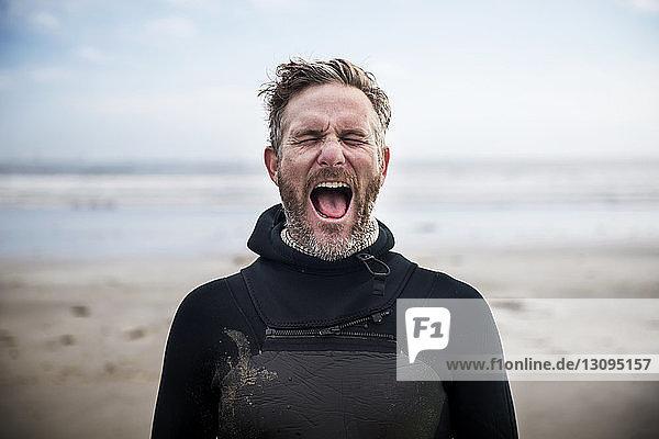 Männlicher Surfer schreit  während er am Strand steht