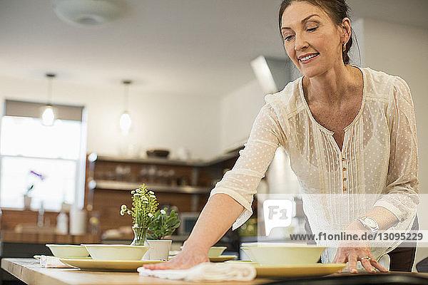 Frau arrangiert Tisch zu Hause