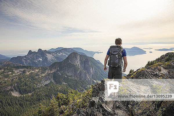Rear view of carefree hiker with backpack walking on mountain against sky