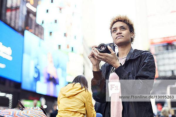 Nachdenkliche junge Frau mit Kamera in der Stadt an einem sonnigen Tag