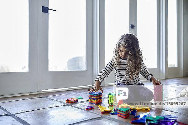 Süßes Mädchen spielt zu Hause auf dem Boden kniend mit bunten Spielzeugklötzen