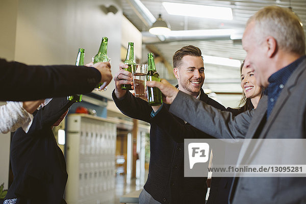 Happy business people toasting drinks in office