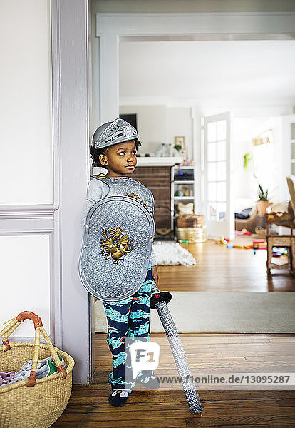Full length of thoughtful boy dressed up in armor costume standing at home