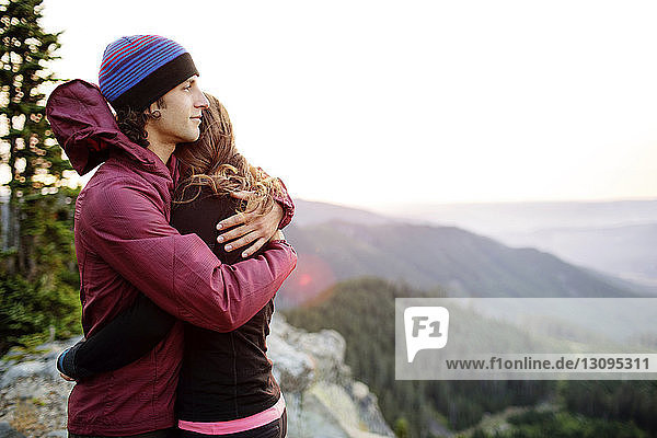 Couple embracing while standing on top of mountain against clear sky