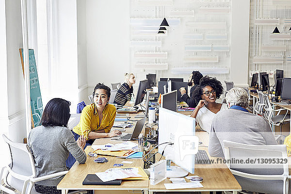 High angle view of business people talking while working in creative office