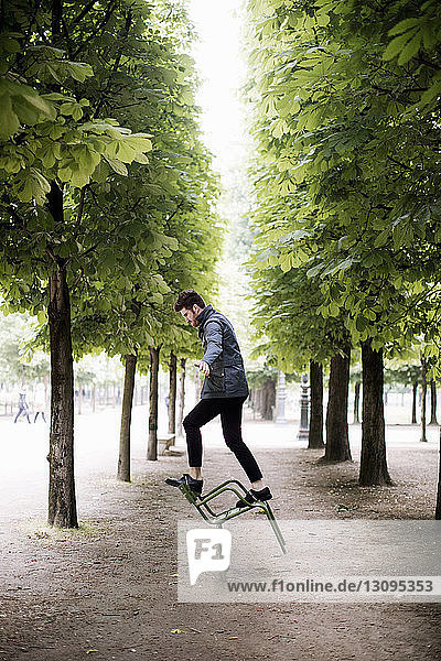 Side view of playful man balancing on tipping chair amidst trees at park