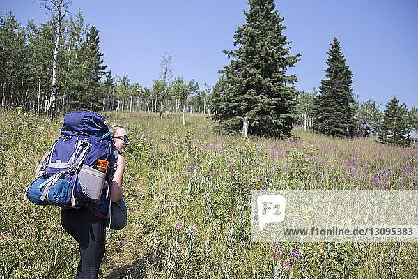 Rückansicht einer Frau mit Rucksack  die auf dem Feld gegen den Himmel läuft