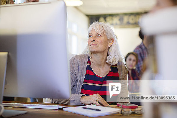 Businesswoman looking away while sitting at desk in office