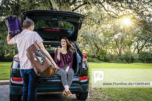 Rückansicht eines Ehemannes  der Gepäck trägt  während die Ehefrau Eiscreme auf dem Kofferraum des Autos auf dem Parkplatz isst