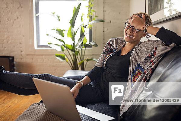 Fröhliche Frau benutzt Laptop auf dem Sofa zu Hause