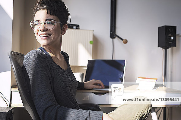 Cheerful woman looking away while using laptop computer at home