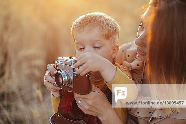 Son photographing with vintage camera by mother on field