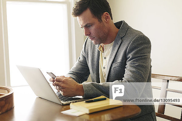 Man using smart phone while sitting with laptop on table at home