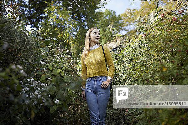 Junge Frau betrachtet Pflanzen  während sie auf dem Feld steht