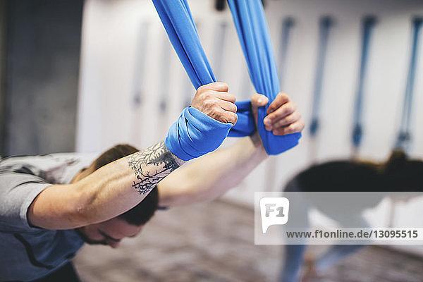 Freunde benutzen Hängematten beim Üben von Yoga im Fitnessstudio