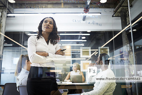 Confident businesswoman looking at glass with colleagues sitting in background