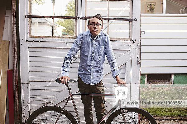 Porträt eines Mannes mit Fahrrad vor einer Garagentür stehend