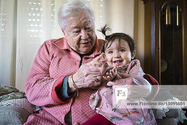 Großmutter spielt mit fröhlicher Enkelin zu Hause