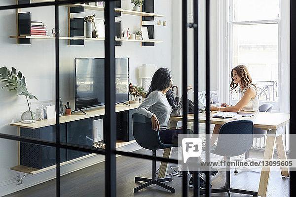Weibliche Kollegen arbeiten zusammen,  während sie am Schreibtisch im Büro sitzen und durch ein Fenster gesehen werden
