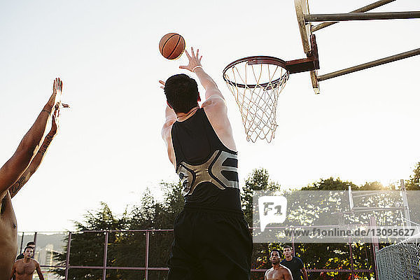 Man playing basketball with friends in court against clear sky